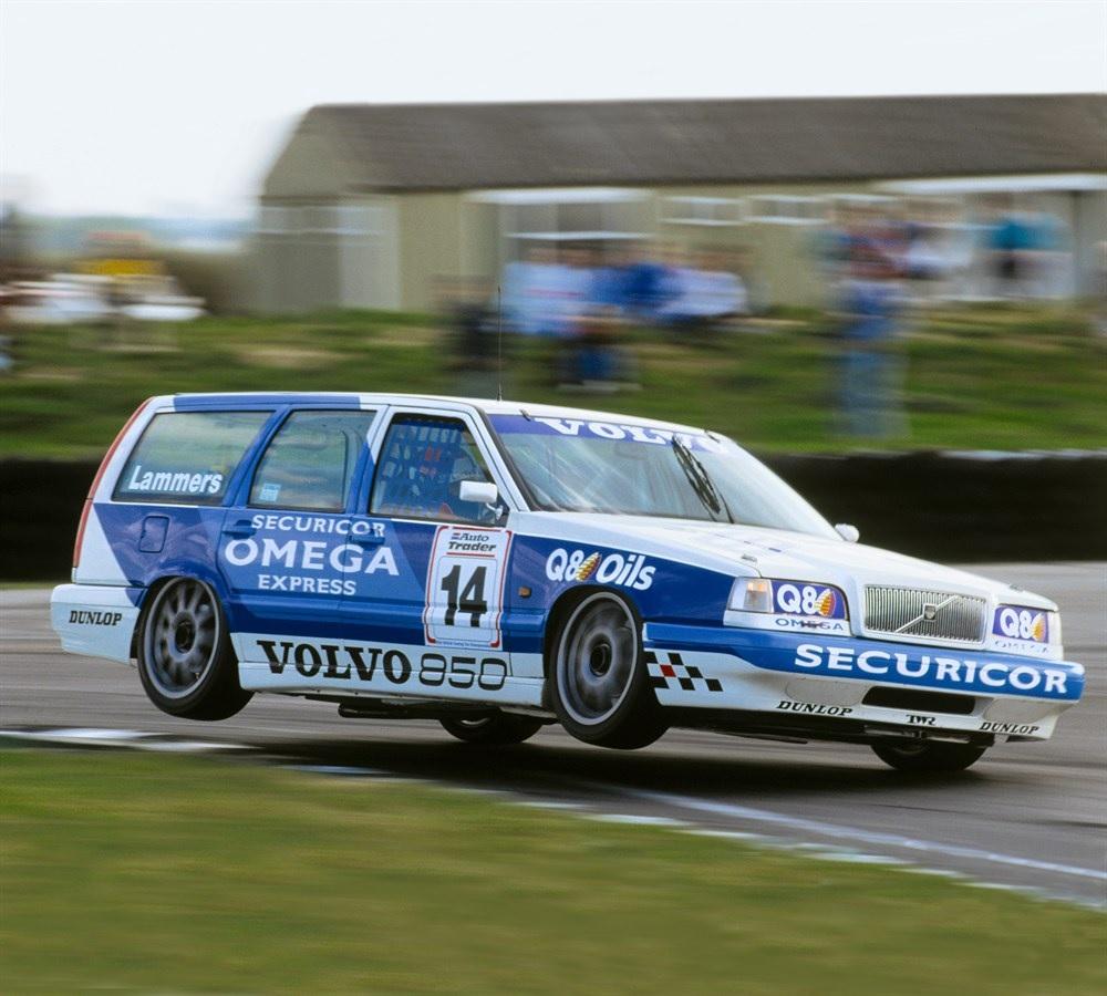 A white-and-blue 1994 Volvo 850 Estate BTCC racer goes up on 2 wheels on a racetrack corner