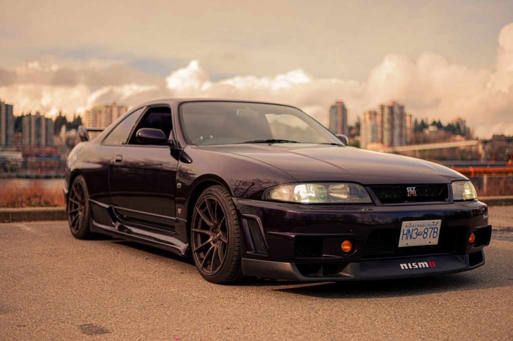 A purple 1995 R33 Nissan Skyline GTR V-Spec parked on a dock