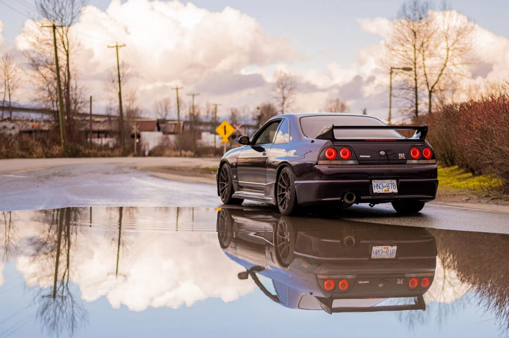 The rear view of a purple 1995 R33 Nissan Skyline GTR V-Spec in front of a puddle