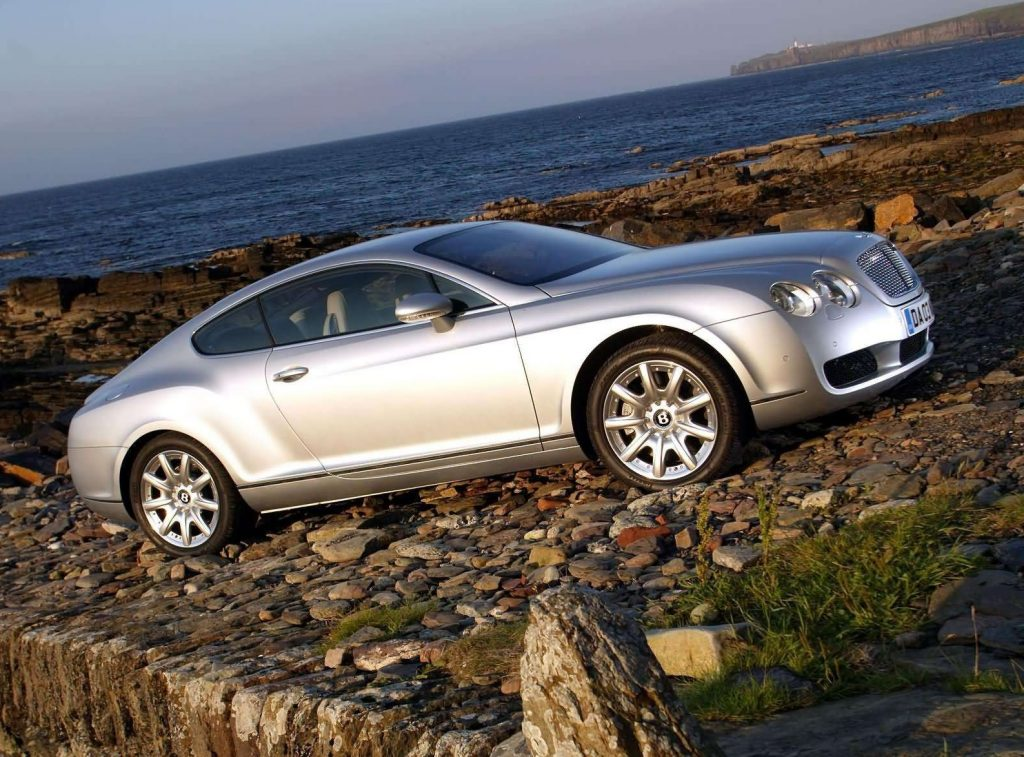 The side view of a silver 2003 Bentley Continental GT parked on a rocky beach