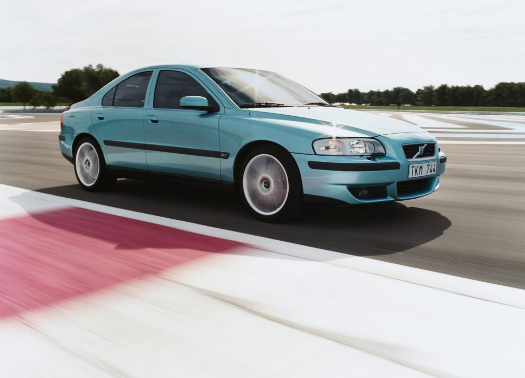 A light-blue 2003 Volvo S60R taking a corner on a racetrack