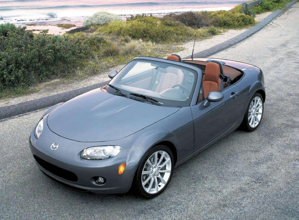 A gray 2006 NC Mazda MX-5 Miata with its roof down