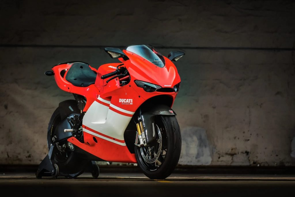 A red-with-white-stripe 2008 Ducati Desmosedici RR on a rear wheel stand