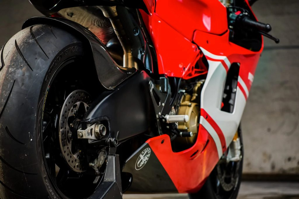 A rear low-angle shot of a 2008 Ducati Desmosedici RR, showing the carbon-fiber swingarm and part of the V4 engine