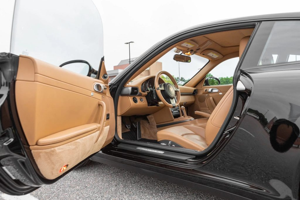 A interior shot of a gray 2011 Porsche 911 4's tan-leather interior, as seen with the driver's door open