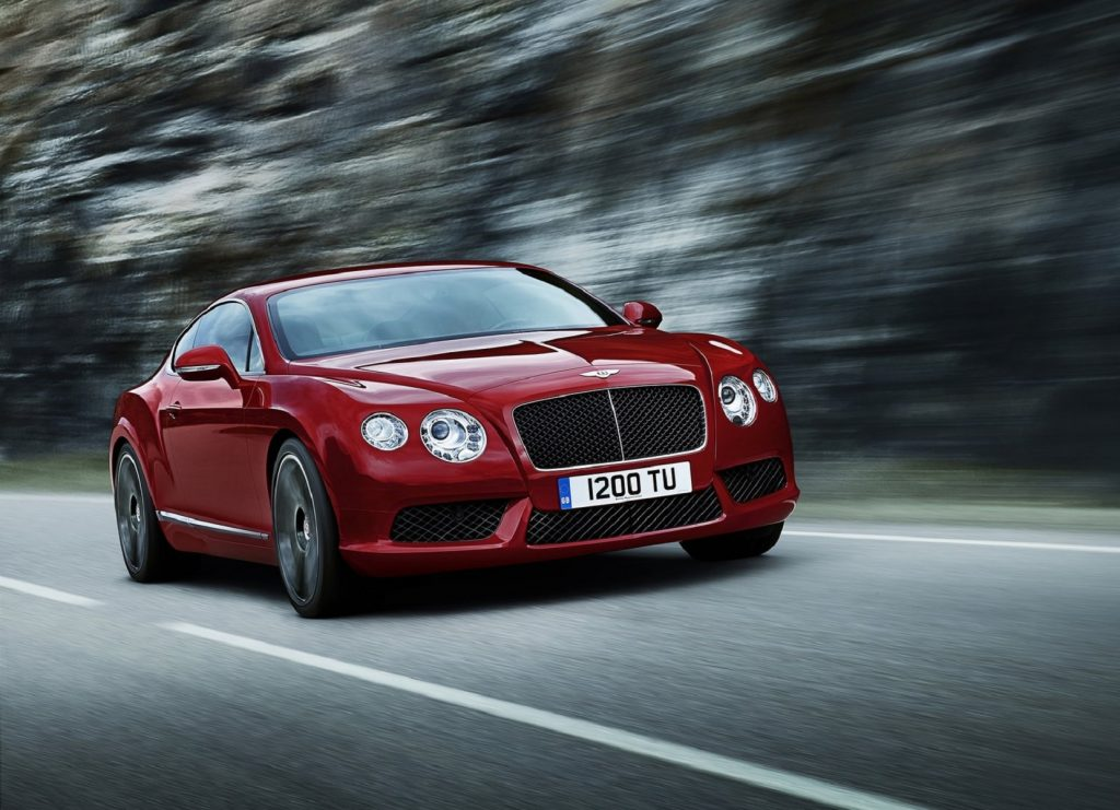 A red 2013 Bentley Continental GT V8 drives quickly down a forest road