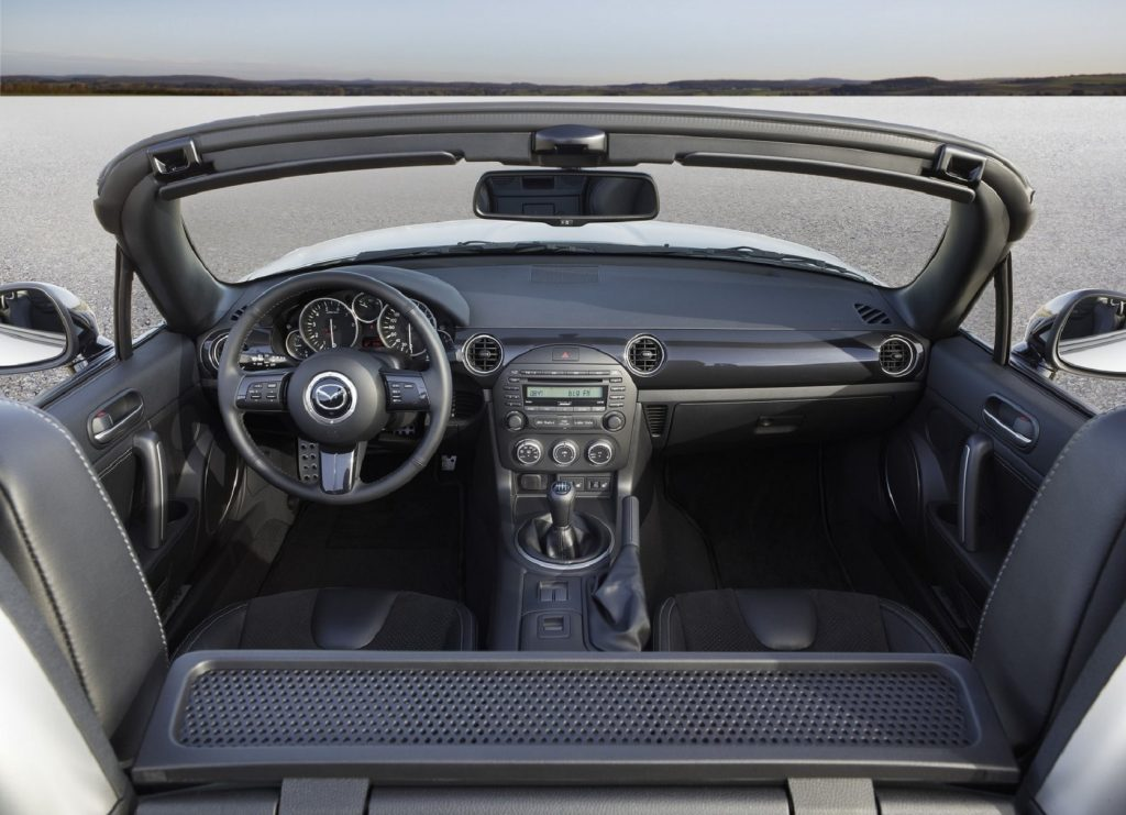 The black interior of a 2013 Mazda MX-5 Miata with its roof down