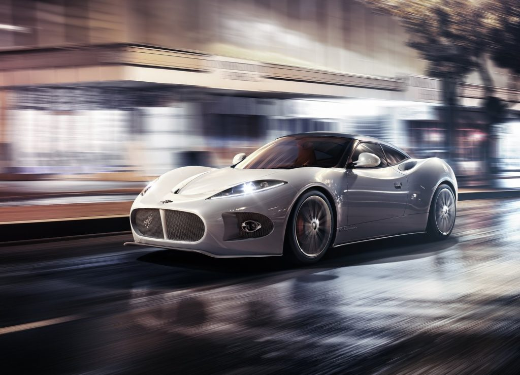 A white 2013 Spyker B6 Venator Concept drives through a brightly-lit city at night