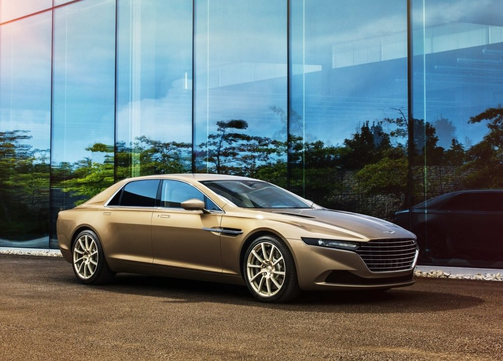 A gold 2015 Aston Martin Lagonda Taraf in front of some glass windows
