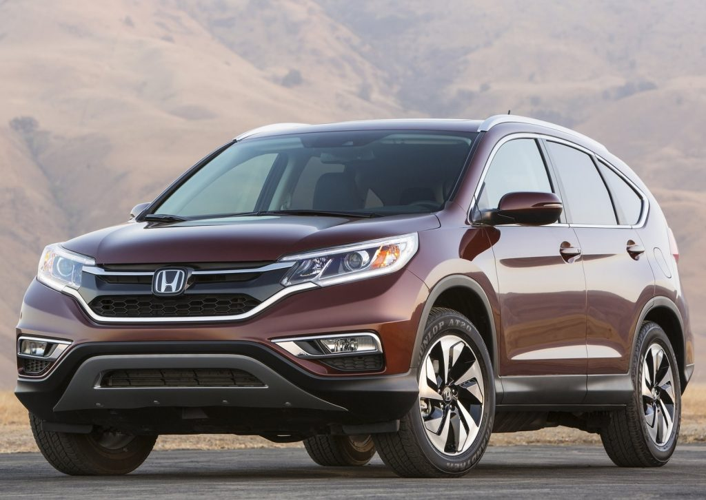 a 2015 honda cr-v in a burgundy color parked with a mountainous backdrop
