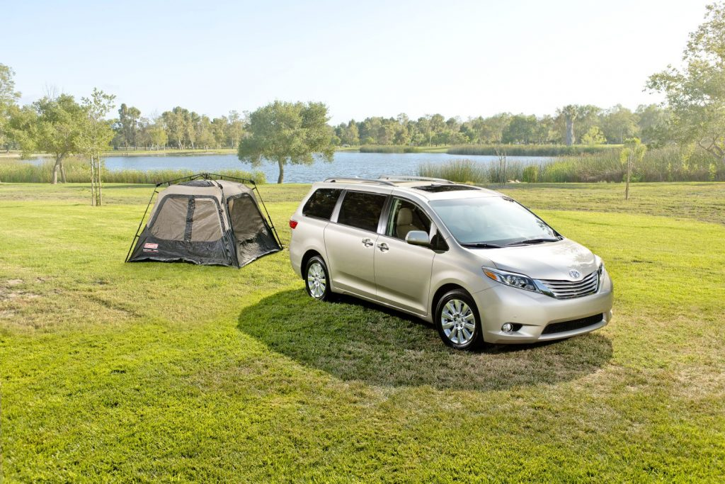 a sliver Toyota Sienna in a natural area, set up for camping
