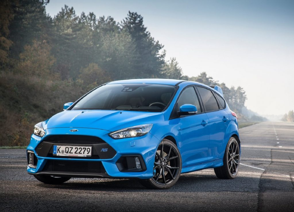 A blue 2016 Ford Focus RS on a tree-lined misty road