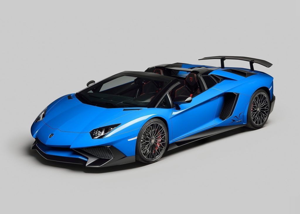 A blue 2016 Lamborghini Aventador SV Roadster in a studio with its roof down