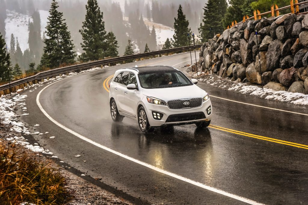 2017 Kia Sorento driving through a snowy and icy mountain road with evergreen trees and rocks in the background