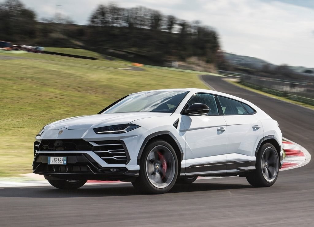 A white 2019 Lamborghini Urus takes a corner on a racetrack