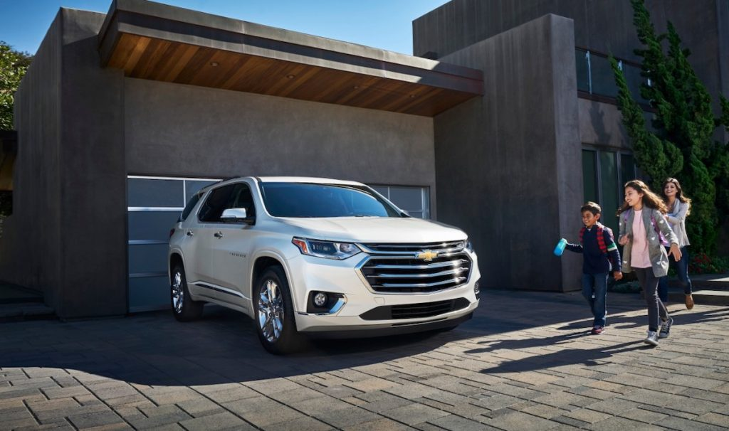 2020 Chevrolet Traverse parked outside a house with a family excited to get into the SUV