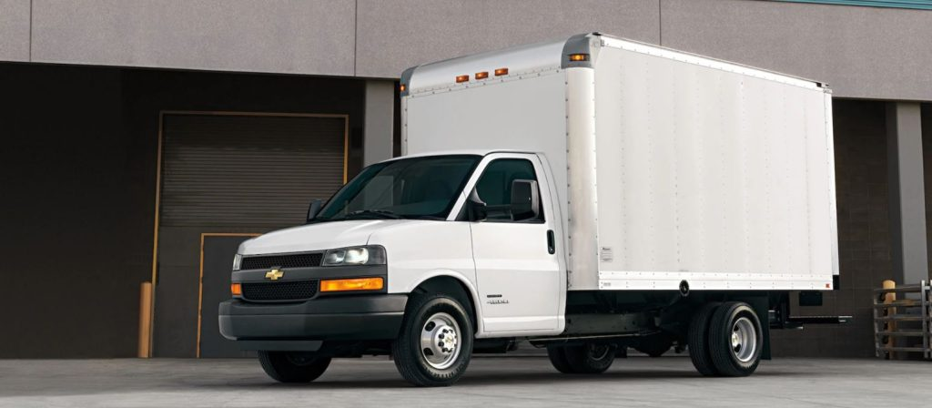 A white commercial box truck sit by a loading dock.