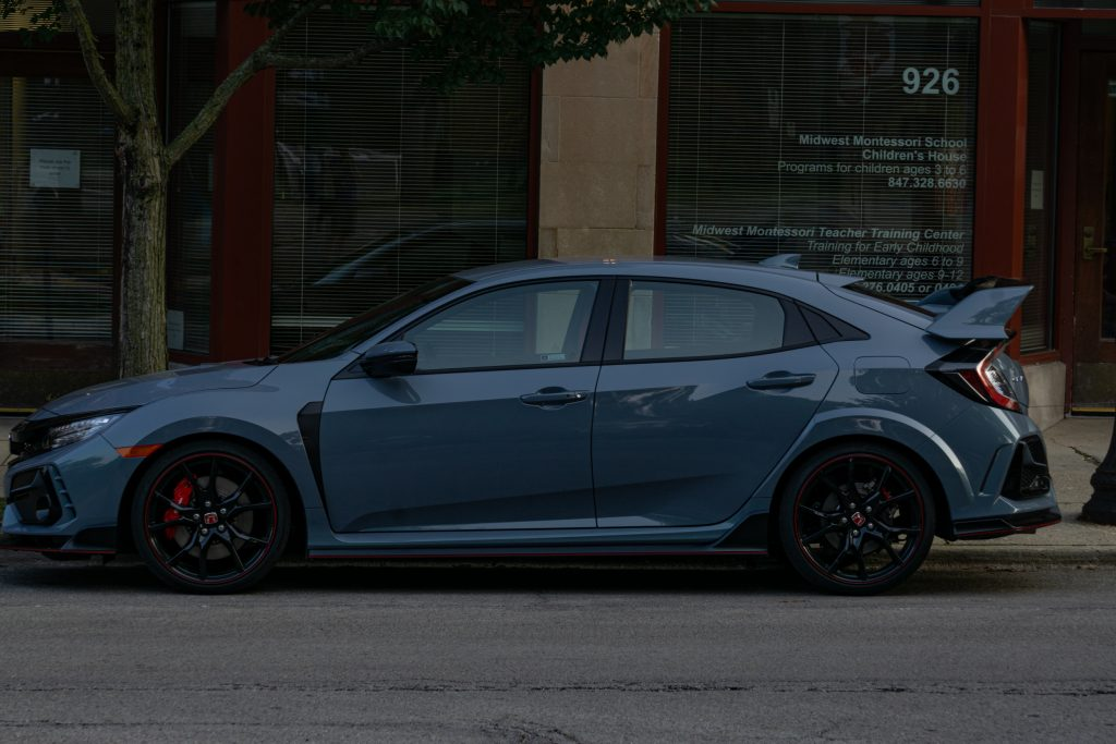 The side view of a gray 2020 Honda Civic Type R on a city street