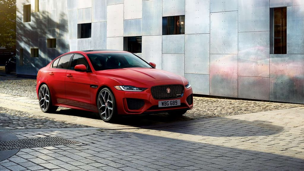 A red 2020 Jaguar XE sedan moves over a brick roadway by a building.