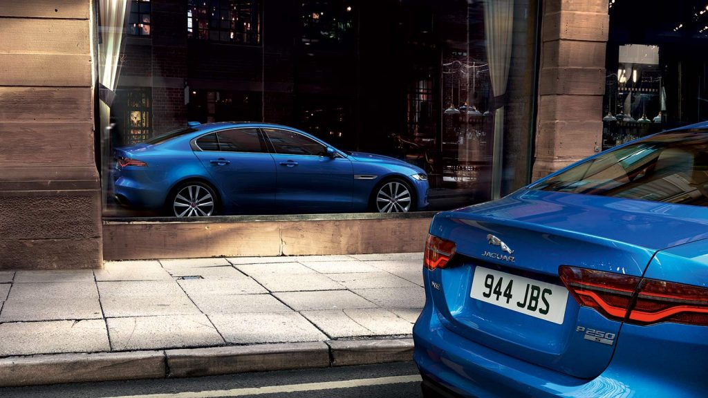 A blue 2020 Jaguar XE P 250S sedan is parked in front of a storefront. The reflection of the sedan is seen in full on the glass of the establishment.