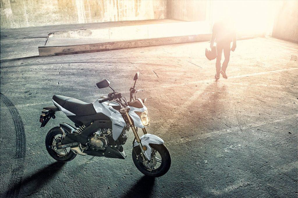 A white 2020 Kawasaki Z125 Pro in a sunny parking garage