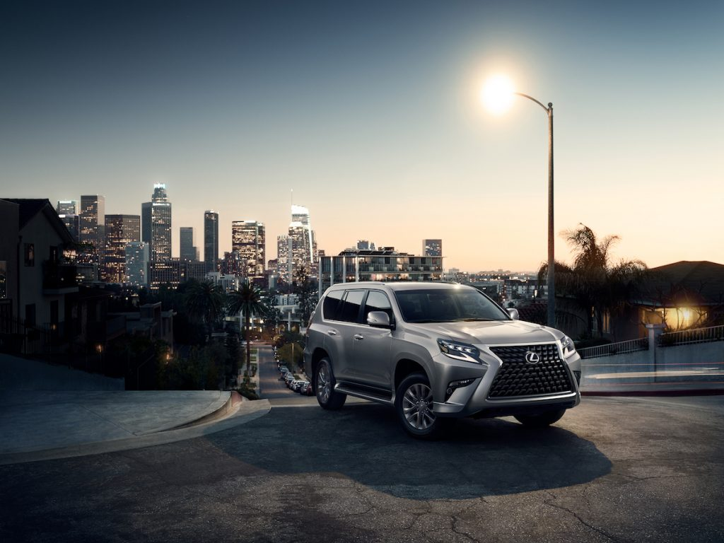 2020 Lexus GX driving away from the city skyline