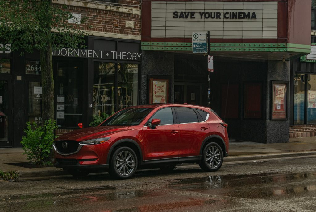A red 2020 Mazda CX-5 Signature AWD on a rainy city street