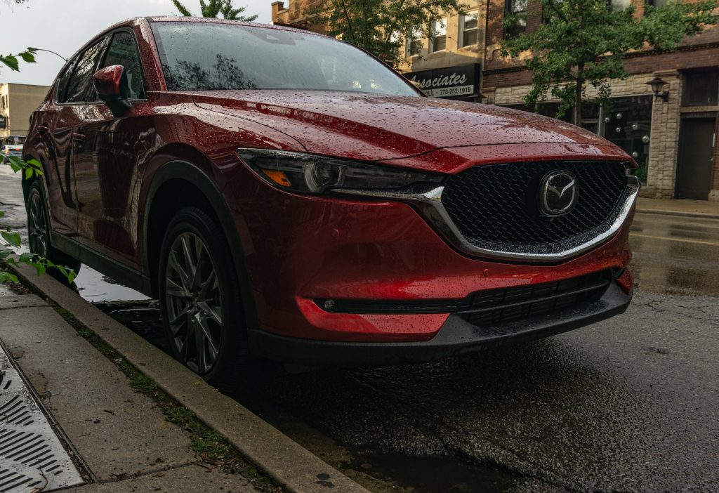 A front-3/4 view of a red 2020 Mazda CX-5 Signature AWD parked on a rainy street