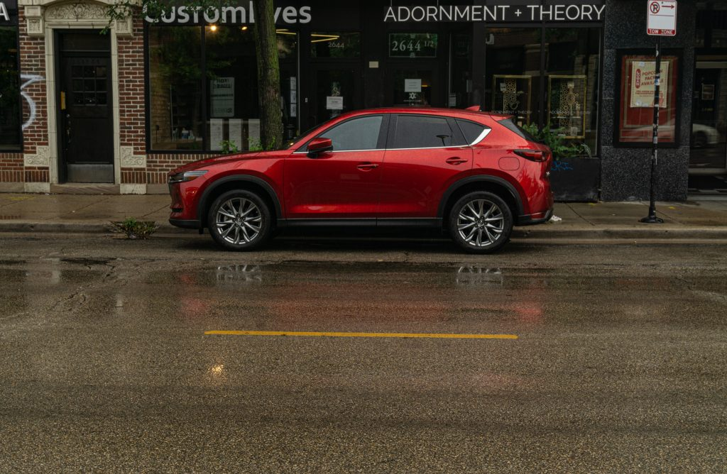 The side view of a red 2020 Mazda CX-5 Signature AWD on a rainy city street