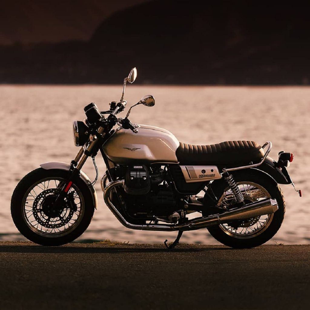 A white-tanked 2020 Moto Guzzi V7 III Special in front of a body of water at sunset