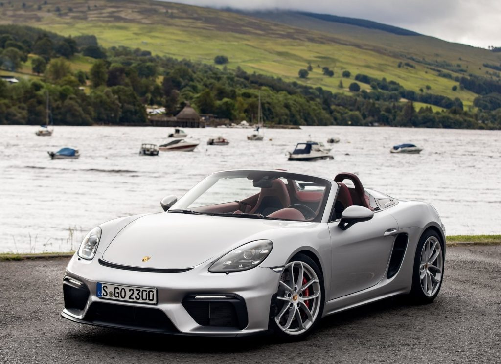 A silver 2020 Porsche 718 Spyder in front of a boat-filled lake