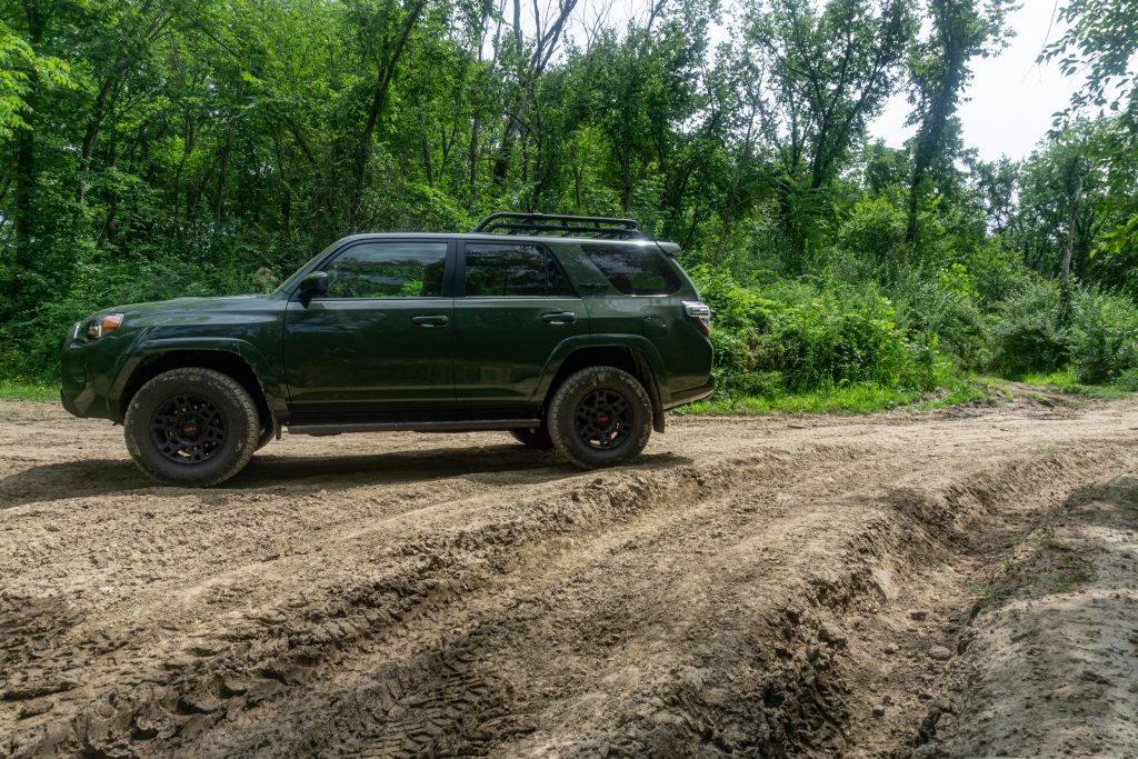 A green 2020 Toyota 4Runner TRD Pro on a forested muddy rutted off-road trail