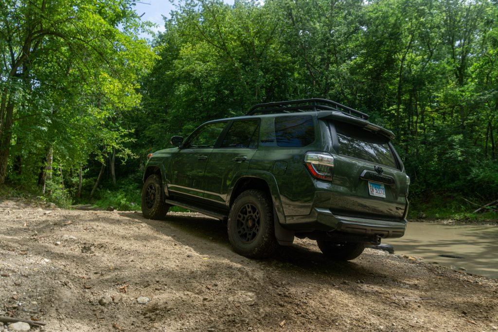 A rear shot of a green 2020 Toyota 4Runner TRD Pro on a forest off-road trail near a creek