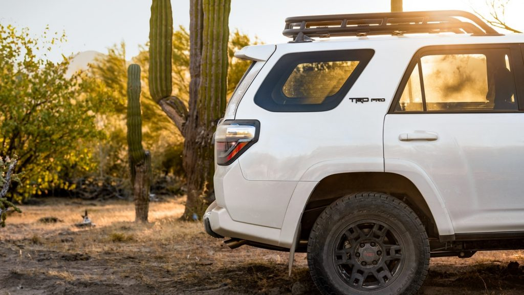 The rear half of a white 2020 Toyota 4Runner TRD Pro in the desert, showing the thick C-pillar and roof rack
