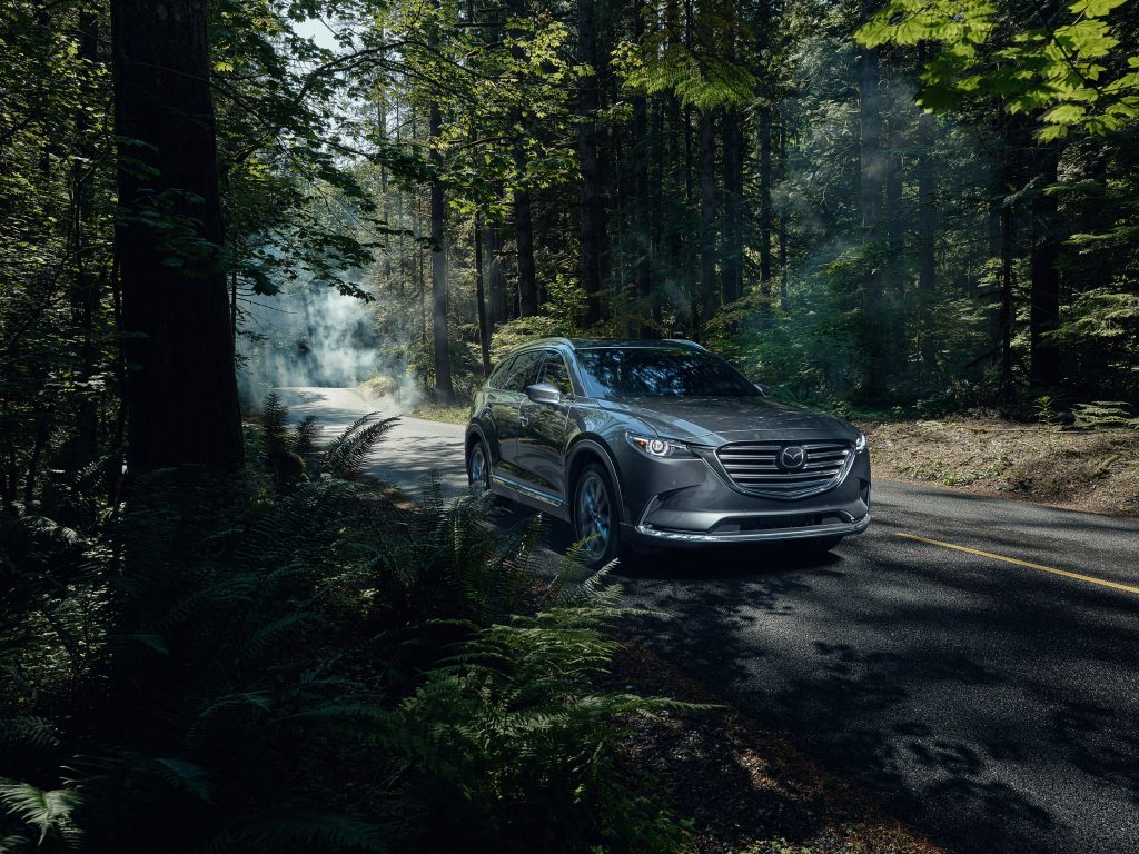 the 2020 Mazda CX-9 driving on a scenic forested back road