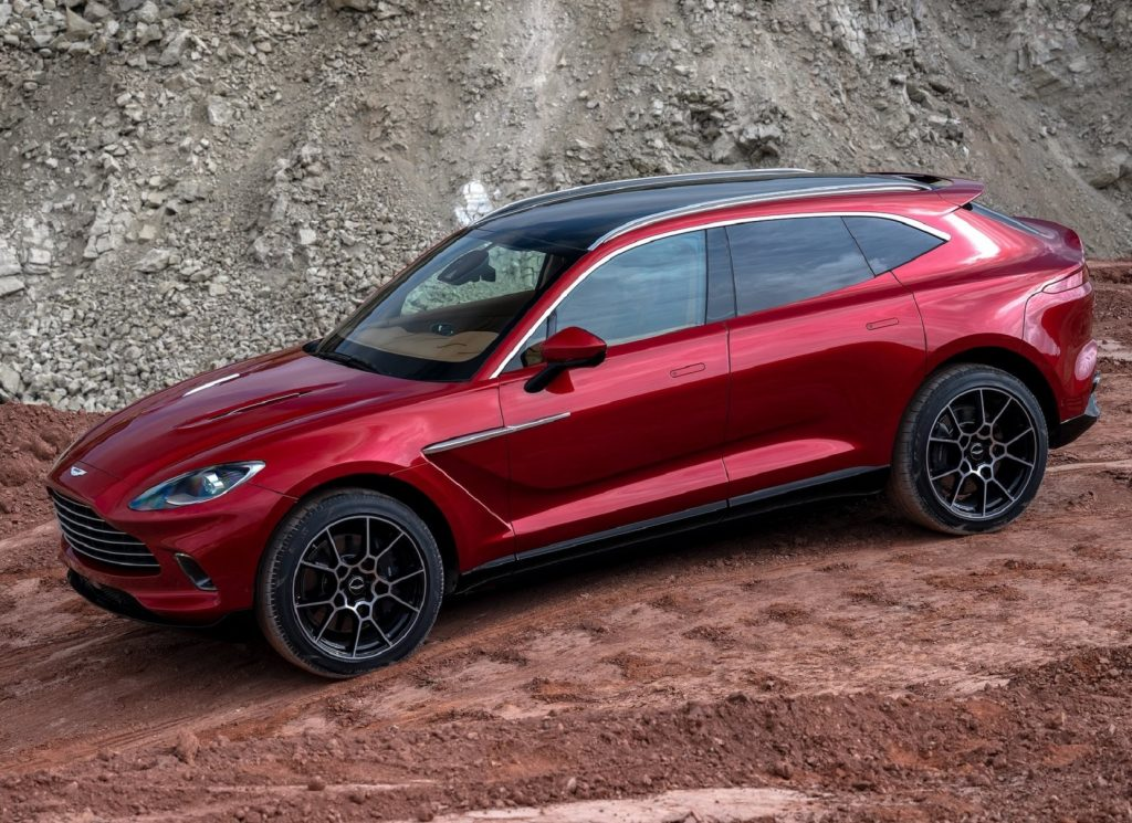 The side view of a red 2021 Aston Martin DBX as it descends a rocky trail