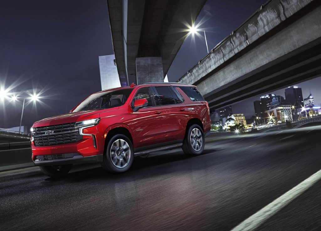 A red 2021 Chevrolet Tahoe drives on a city's highway at night