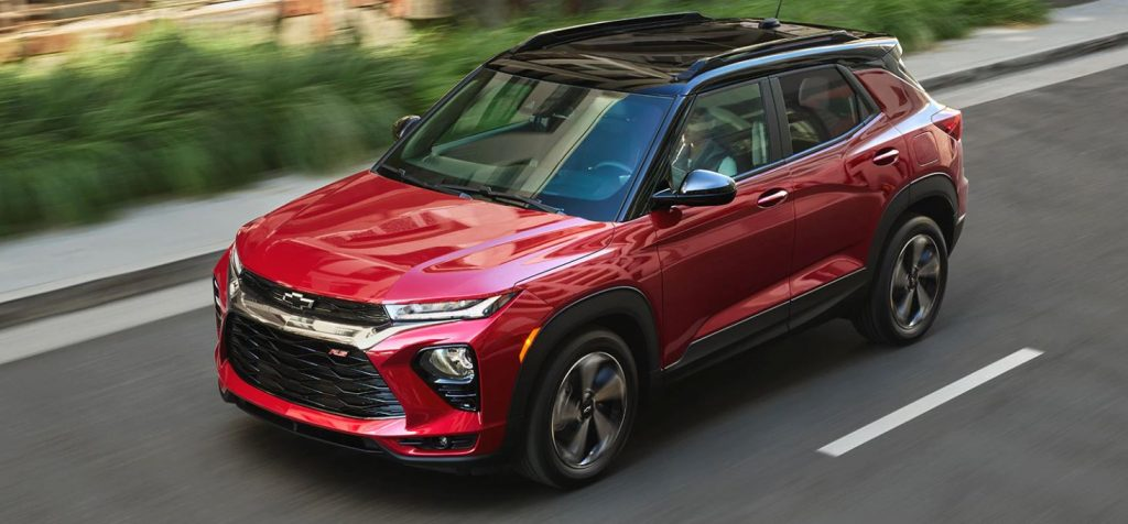 A red 2021 Chevrolet Trailblazer with a block top drives down a road.