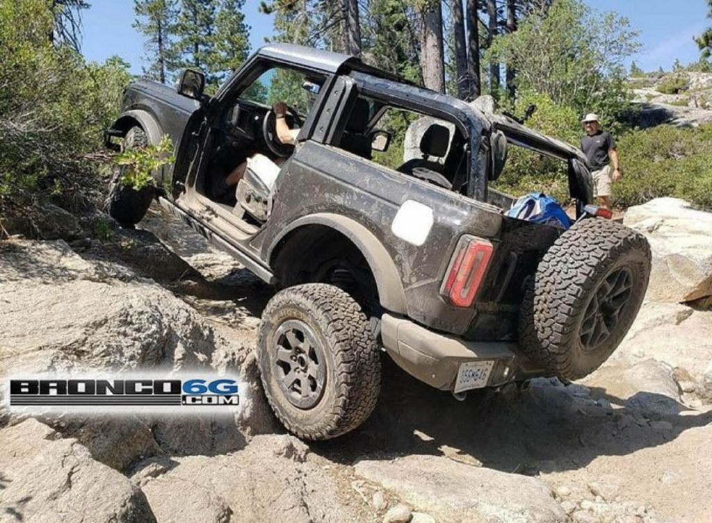 A black 2-door 2021 Ford Bronco with its doors and roof removed scrambles up a rocky incline on the Rubicon Trail
