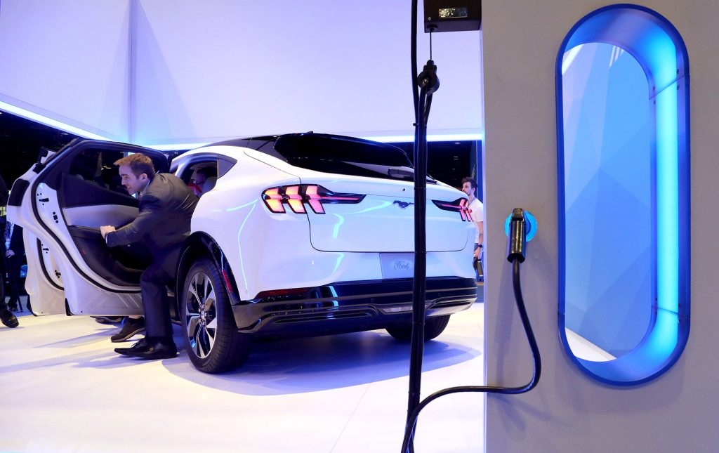 The rear of a white Ford Mustang Mach-E sits by an electric charging station.