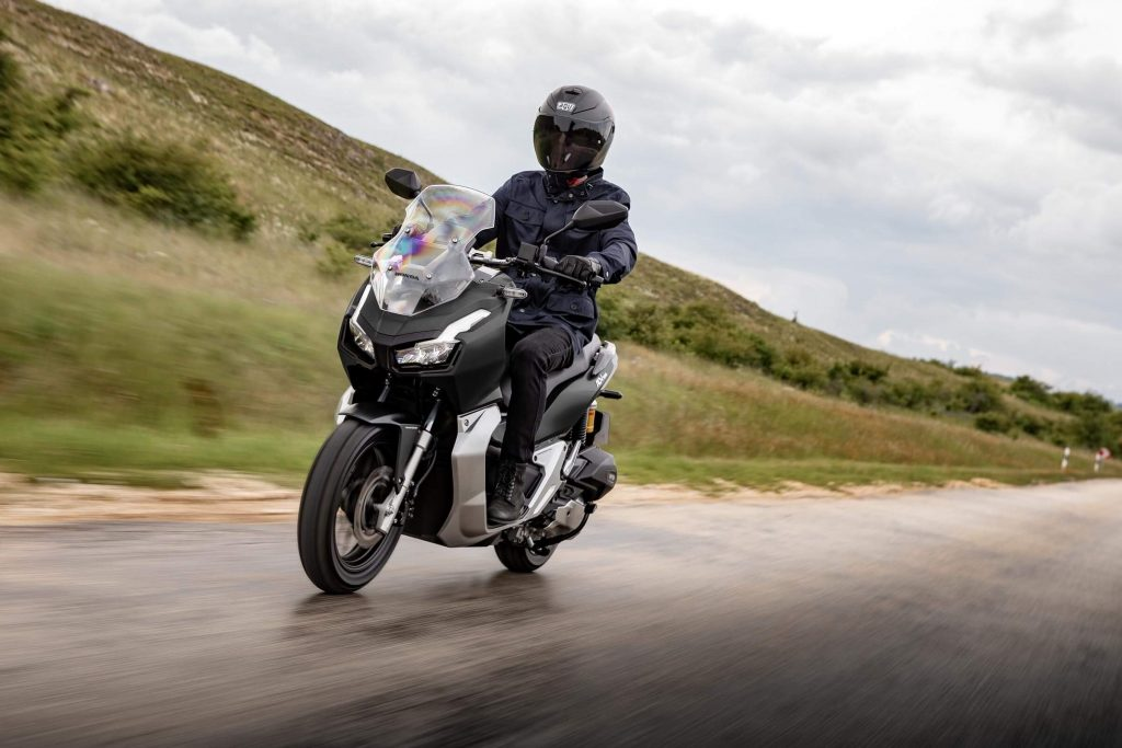 A black 2021 Honda ADV150 rides down a wet road