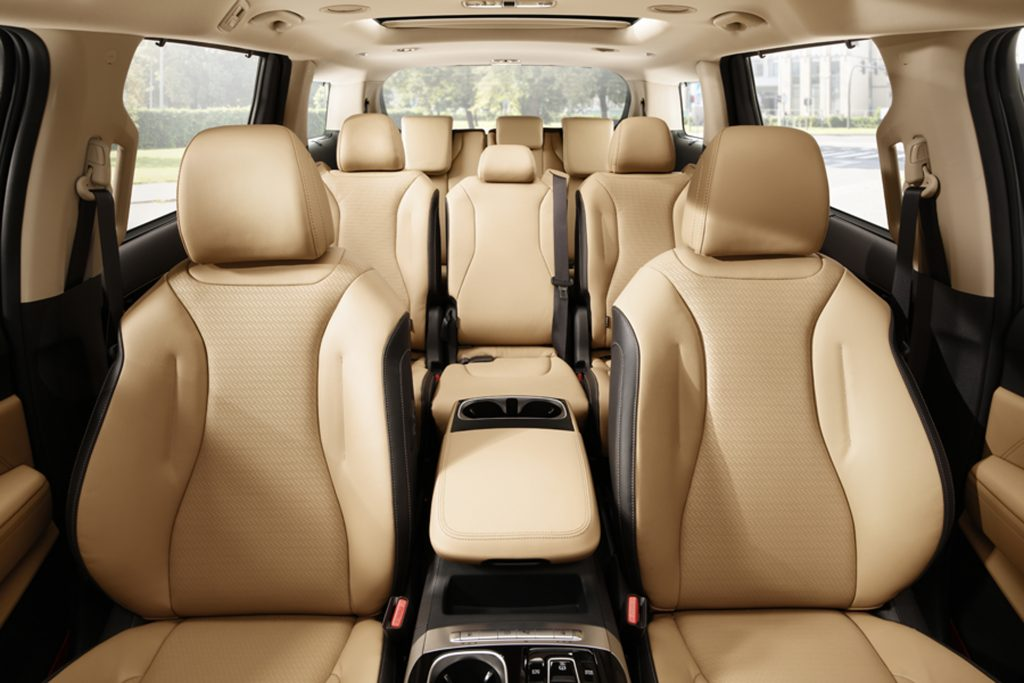 The tan interior of the 2021 Kia Sedona is seen from the front to the back.