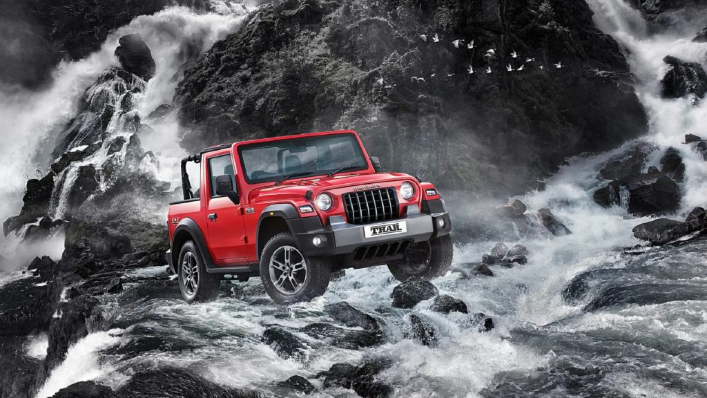 A red 2021 Mahindra Thar with its roof off crosses a roaring river