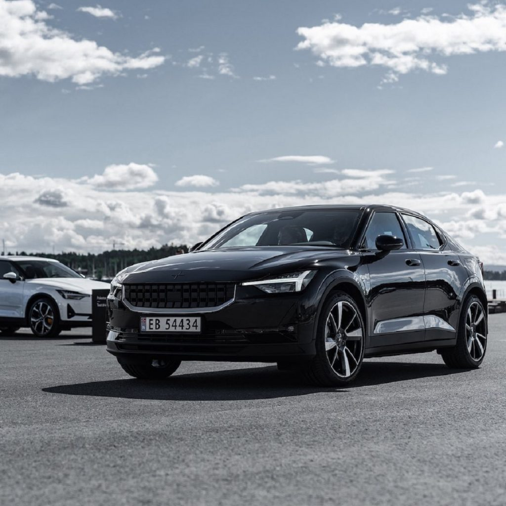 A black 2021 Polestar 2 with a white one in the background