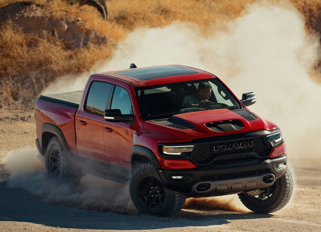 A red 2021 Ram 1500 TRX slides through the desert in a big dust cloud