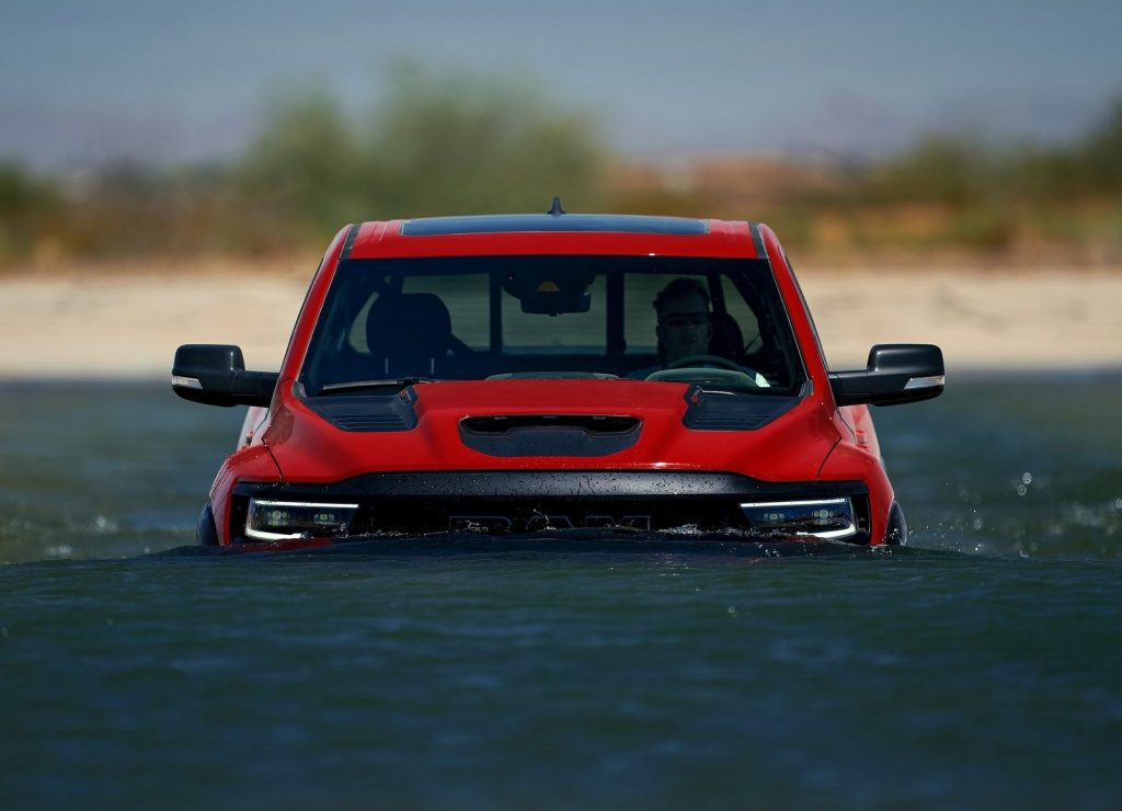 A red 2021 Ram 1500 TRX wading through deep water
