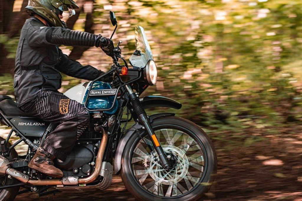 A rider guides a blue-and-white 2021 Royal Enfield Himalayan through a forest