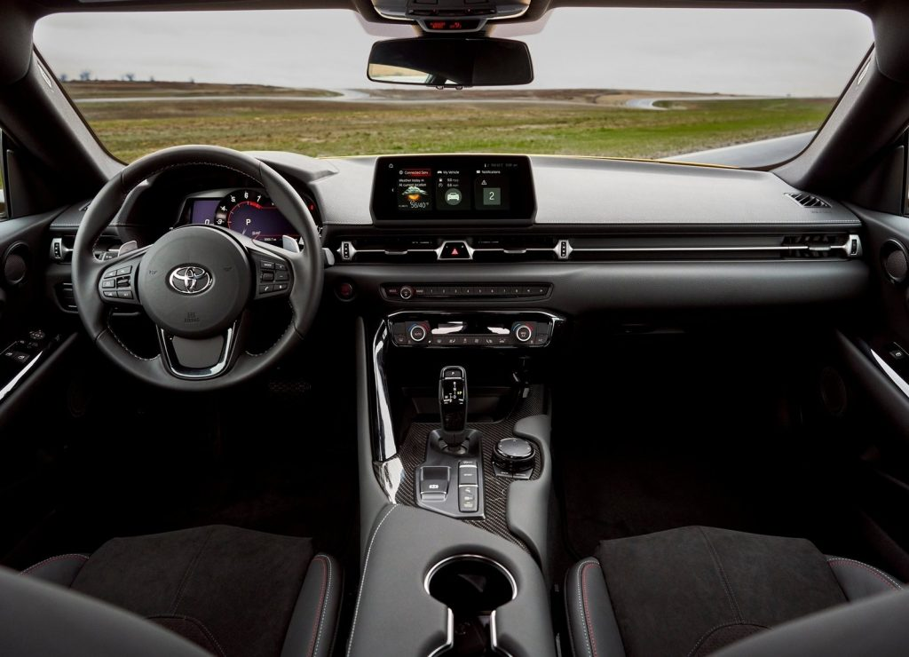 The interior of a 2021 Toyota Supra 2.0, showing the center touchscreen, carbon-fiber trim, and leather-trimmed sport seats