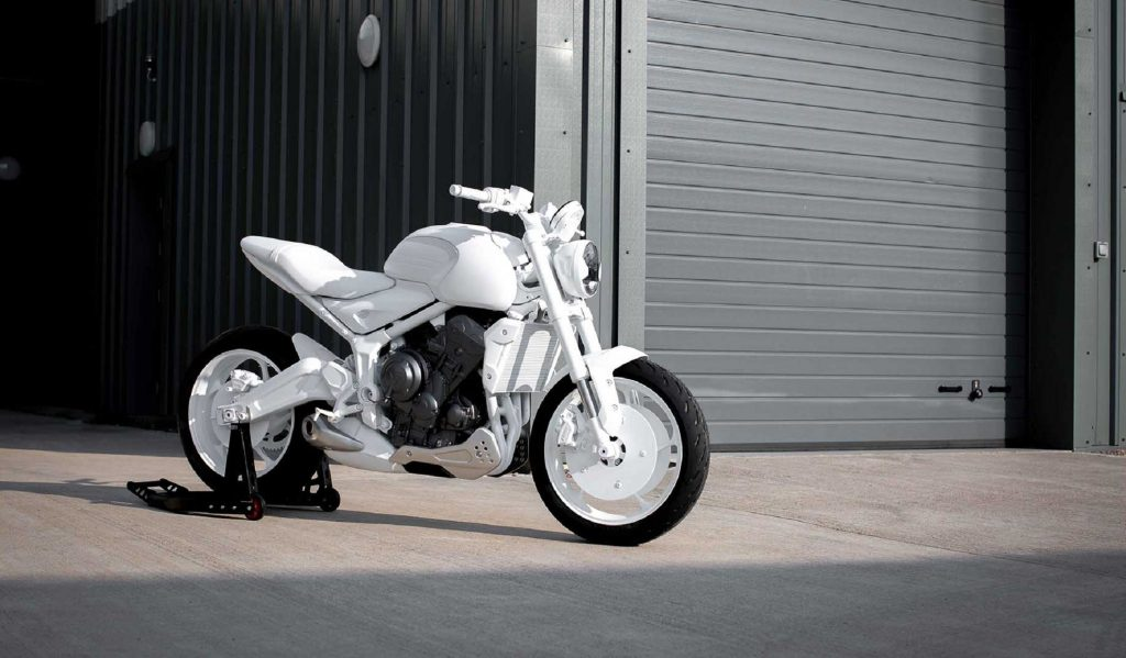 A white 2021 Triumph Trident prototype in front of a garage
