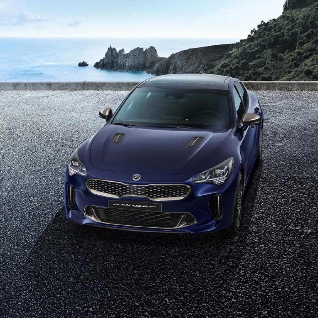 A dark-blue 2022 Kia Stinger on a rocky ocean overlook